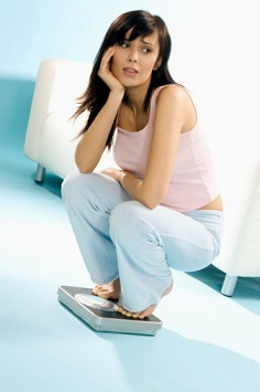 Young woman, squatting on scales, chin in hand