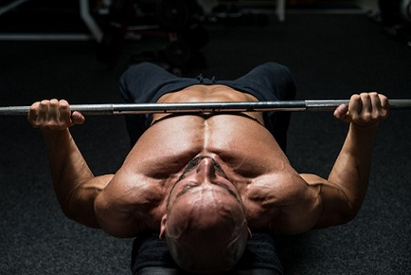 Mature Man In Gym Exercising On The Bench Press