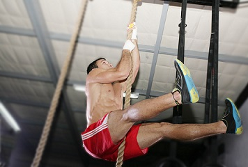 Crossfit rope climb exercise. Focus in the body